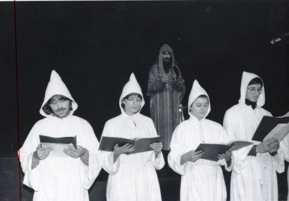 Black and white photograph of two young women and two young men, holding open notebooks. They wear white tunics, with hoods. Behind them, a bearded man wearing a striped, multicoloured tunic with a hood, standing in front of a microphone.
