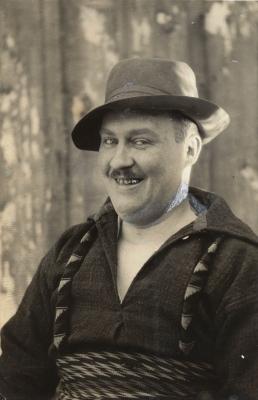Photographie portrait en noir et blanc d'un homme d'âge mûr souriant. Il arbore la moustache. Il est vêtu d'une chemise épaisse, porte un chapeau et une ceinture fléchée.