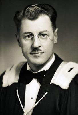 Photographie en noir et blanc, prise dans un studio, d'un homme d'âge moyen, vu de face et en gros plan, portant des lunettes et une petite moustache. L'homme a revêtu un smoking, un nœud papillon et une épitoge en fourrure.