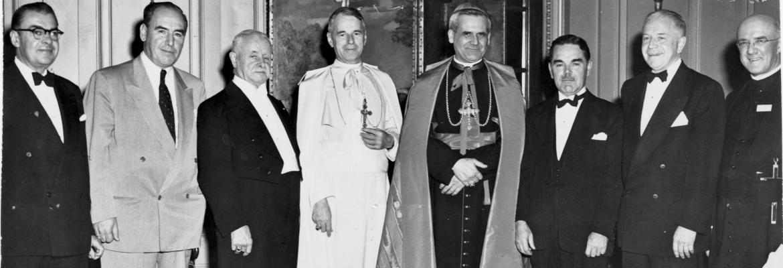 Photographie en noir et blanc d'un groupe d'hommes, d'âges divers, en habits de soirée. Le groupe inclut trois religieux portant les vêtements liturgiques d'un évêque pour le premier, ceux d'un archevêque pour le second et la soutane pour le troisième.