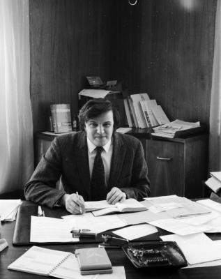 Photographie en noir et blanc d'un jeune homme travaillant à un bureau en désordre. L'homme porte un complet et une cravate. Il sourit à la caméra.