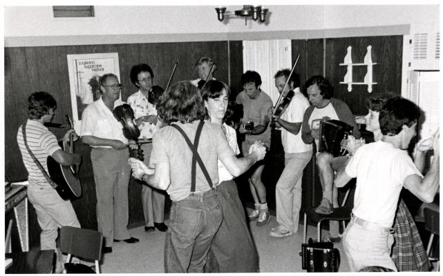 Photographie en noir et blanc d'une soirée dansante. Deux couples de jeunes adultes dansent au centre d'un demi-cercle formé par quatre violoneux, deux guitaristes et un accordéoniste. Les musiciens sont tous des hommes.