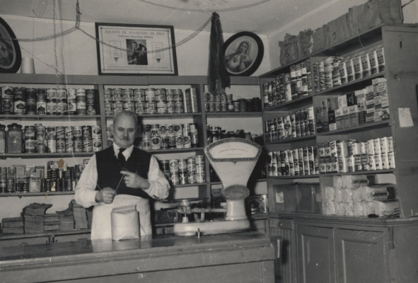 Black and white photograph of an older man preparing a bag at the counter of a store. Behind him, shelves filled with cans and other staples.