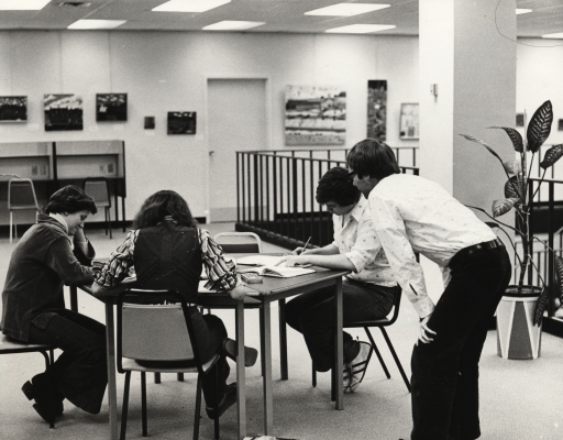 Black and white photograph of two young women and a young man sitting around a table in a study room. An adult, seen from the back, is leaning over, watching them work.