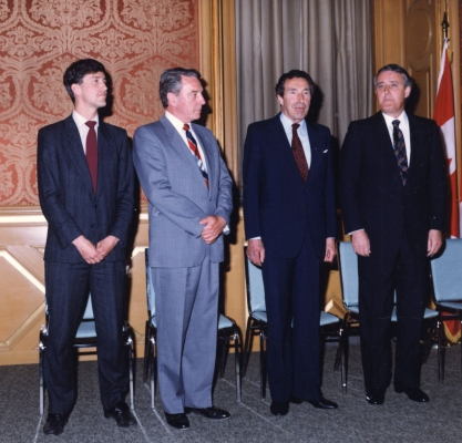 Colour photograph of a young man and three older men, all wearing suits and ties. They are standing in front of white chairs, with the Canadian flag visible on the far right, suspended from a short flag pole.