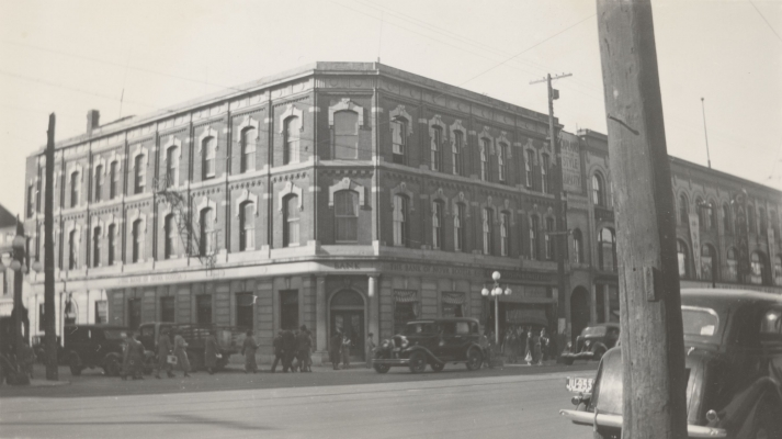 Black and white photograph of a three-story brick building with many windows. It is located on a busy street. Engraved in stone, above the main entrance and on the sides, the Bank of New Scotia name.