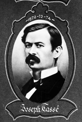 Photographie prise en studio, en noir et blanc, d'un jeune homme moustachu au regard sévère. L'homme est vu de trois quarts et porte un veston noir, un nœud papillon et une chemise blanche à col montant. La photographie, de forme ovale, est entourée d'un cadre décoratif.