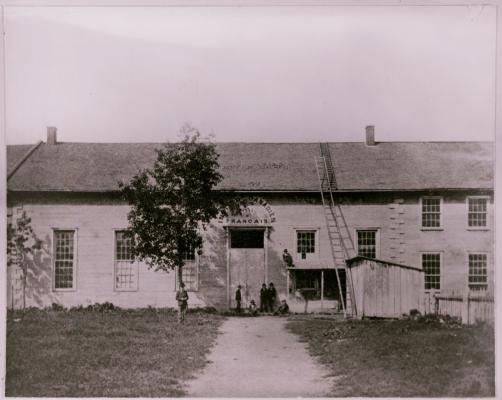 Photographie en noir et blanc d'un long édifice à deux étages en pierre, orné de fenêtres. Au dessus de l'entrée principale, une enseigne de l'Institut canadien-français. Sept hommes se tiennent près de l'entrée principale, dont un juché sur le toit d'un portique.  Une longue échelle rejoint le toit.
