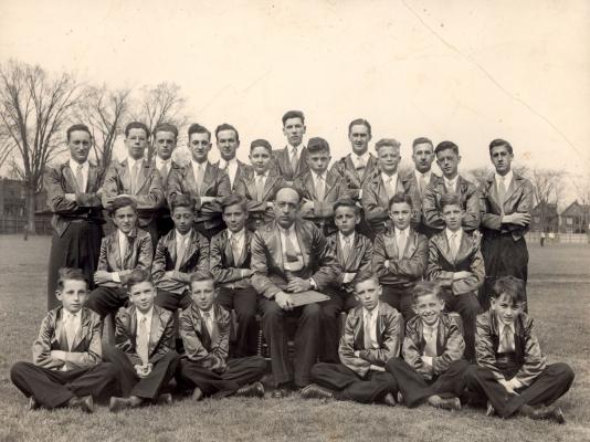 Photographie en noir et blanc d'un groupe de jeunes gens, prise dans un champ. Certains sont assis sur le sol, d'autres sur des chaises, les derniers sont debout à l'arrière.  Un homme d'âge mûr tenant un cartable est assis au centre du groupe. Tous portent un pantalon noir, un veston gris luisant et une cravate.