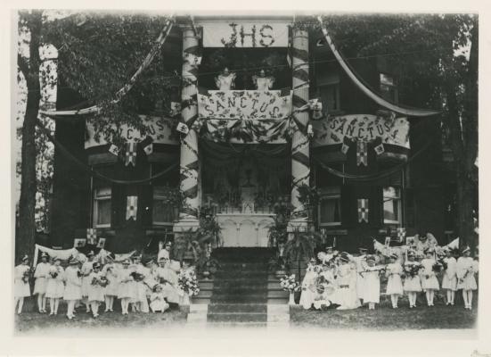 Photographie en noir et blanc d'un reposoir, à l'avant d'une maison de trois étages, richement décorée de bannières et de banderoles. Sur un des balcons, deux statues d'anges. Au pied du reposoir, une trentaine de jeunes enfants habillés de blanc, portant des couronnes et des ailes et tenant des bouquets de fleurs.