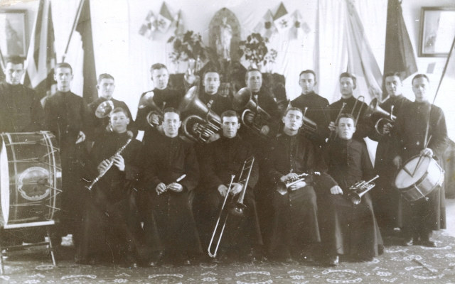 Photographie en noir et blanc d'un groupe d'une quinzaine de musiciens, d'âges divers. Cinq d'entre eux sont assis, les autres sont debout derrière. Tous portent la soutane et tiennent leur instrument.