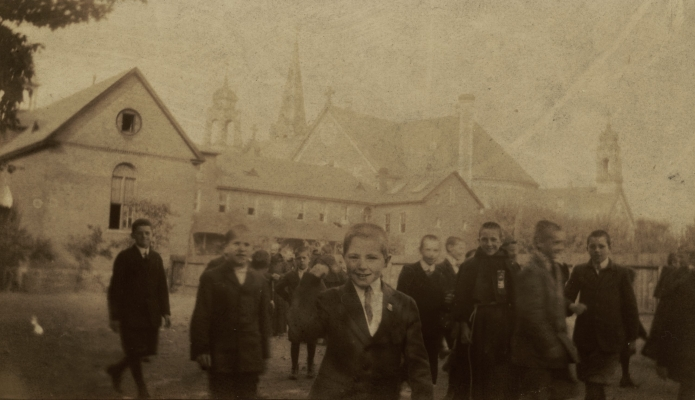 Sepia photograph of a group of twenty-some smiling young boys wearing suits and ties. They mill about in front of a group of religious buildings, with monks in the background talking to some of the boys.