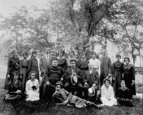 Photographie en noir et blanc d'un groupe d'une vingtaine de personnes, des jeunes femmes pour la plupart. Trois hommes plus âgés, dont un prêtre, sont assis au centre de la photo. Un jeune homme est allongé sur le côté devant eux. Les autres sont debout derrière, ou assis par terre, à leur côté. La photographie a été prise dehors, à proximité d'un édifice bordé de grands arbres.