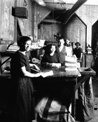 Black and white photograph of three young women and two young men standing at counters. They are surrounded by stacks of newspapers.