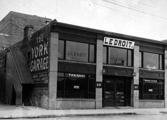 "Black and white photograph of a two-storey brick building with many windows. The sign ""Le Droit"" is hung on the second floor. The words ""The York Garage"" appear on the side of the building. Signs over the first-floor windows read ""TAXI CABS"" and ""TOURING CARS."""