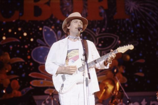 Photographie en couleur d'un homme d'âge moyen moustachu, sur une scène. Il porte un chapeau, un foulard au cou, un costume blanc et un tee-shirt avec un motif coloré. Il joue de la guitare électrique et chante devant un microphone. En arrière-plan, des motifs géométriques sur fond coloré et l'inscription « CBOF-FM ».
