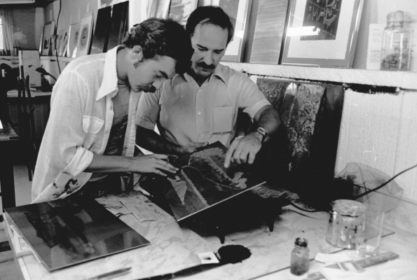Black and white photograph of a middle-aged man and a younger man in an art studio. The two men are examining a work of art. Several paintings are arranged on the floor and the walls.