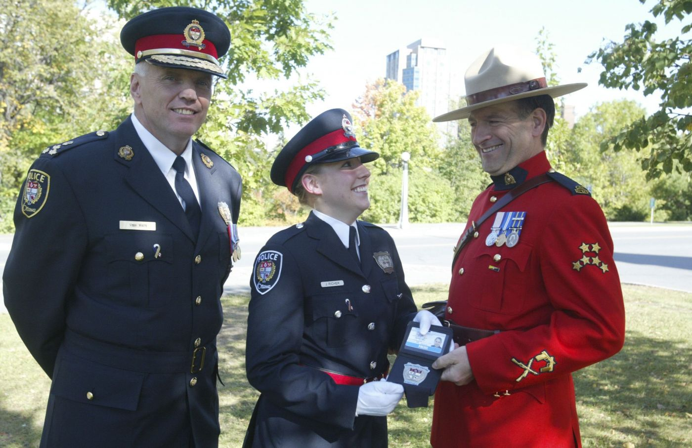 Colour photograph of two older men and a young woman in a park. The woman and one of the men wear the dark blue uniform of the Ottawa police. The other man wears the red uniform of the Royal Canadian Mounted Police. The man in red presents a police badge to the woman; they are looking at each other. The other man looks directly at the camera. All three have big smiles.