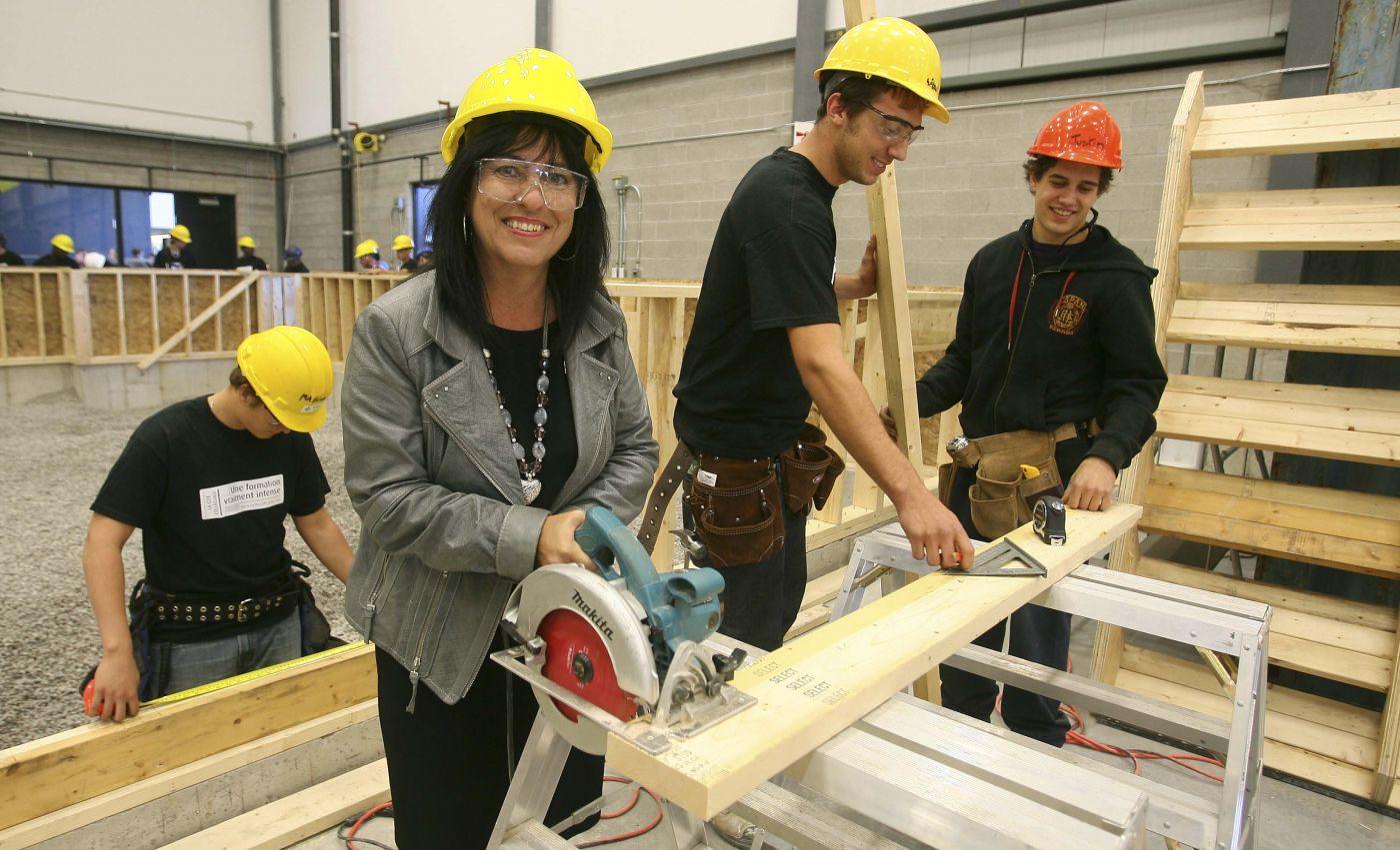 Photographie couleur de trois jeunes hommes et d'une femme d'âge moyen dans un atelier de menuiserie. Ils s'affairent autour d'une planche de bois et tiennent différents outils. Tous portent le casque, la dame porte des lunettes de protection. Elle sourit à la caméra. En arrière-plan, un autre groupe d'ouvriers.