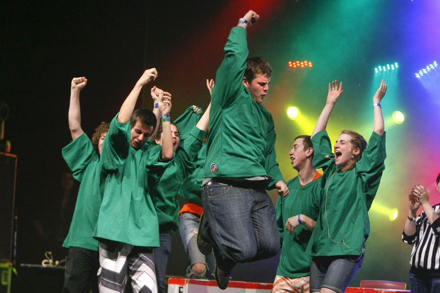 Colour photograph of a group of seven teens wearing green jerseys, celebrating a victory on stage. The young man in the foreground of the photo is jumping with joy, his right fist raised over his head.