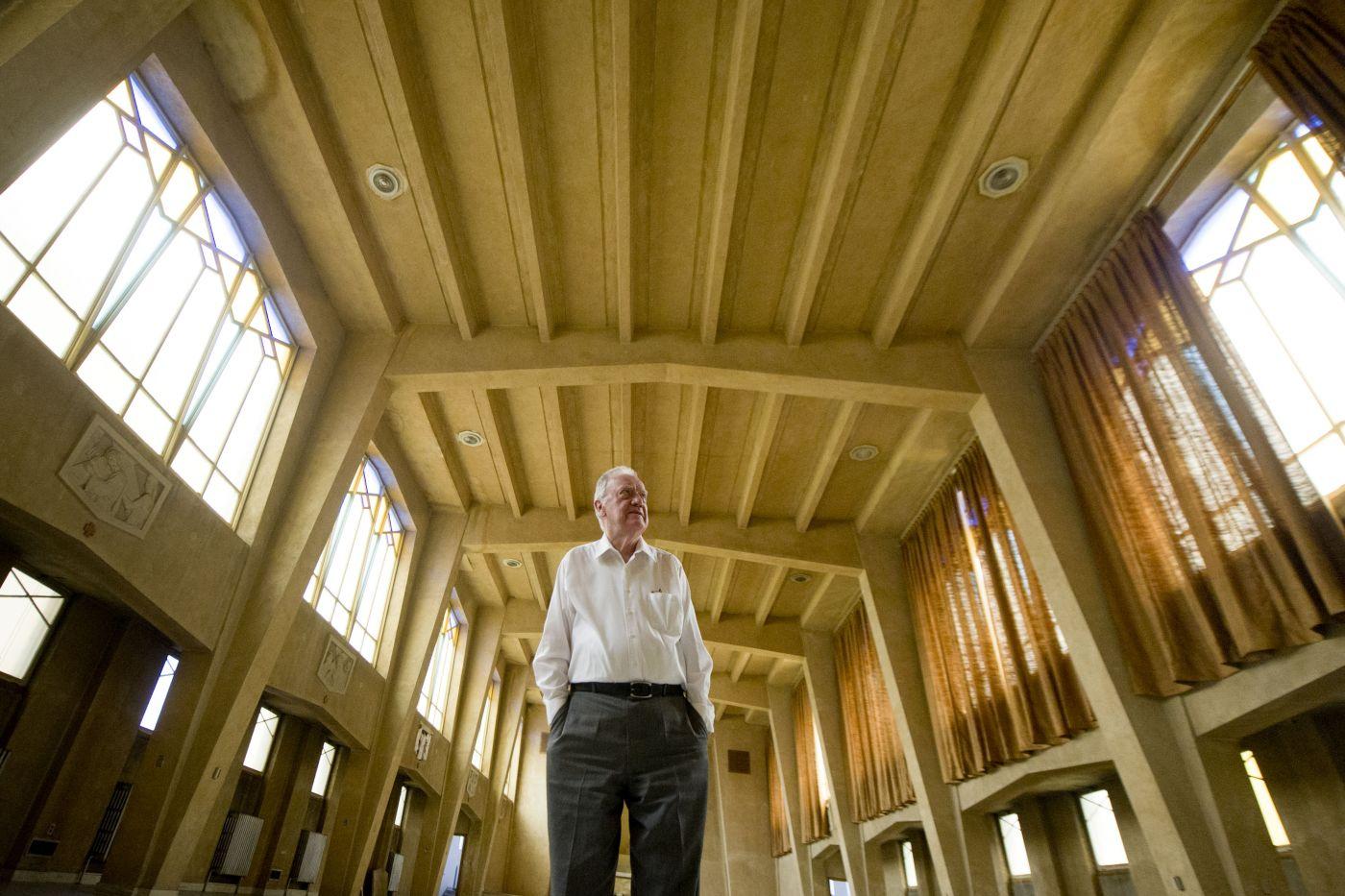 Photographie en couleur d'un homme d'un certain âge aux cheveux blancs, debout au centre d'une église, les mains dans les poches de son pantalon. Le bâtiment est décoré simplement, avec des vitraux et un chemin de croix.