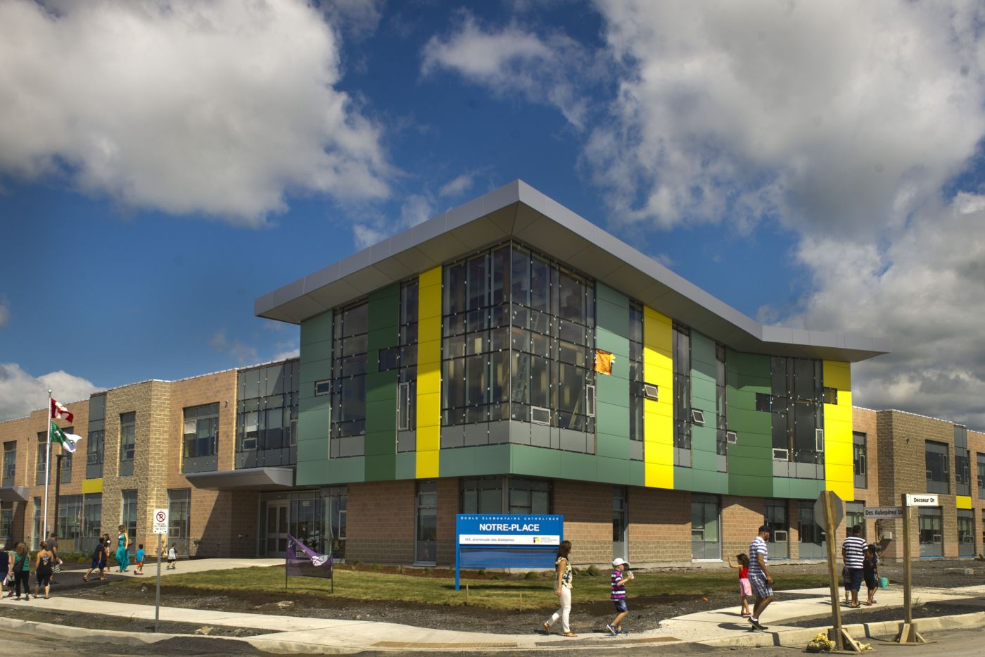 Colour photograph of a two-storey brick and glass building with coloured sections surrounding the glass. Children and parents walk around the building. In the centre, a blue and white sign bearing the name of the school.