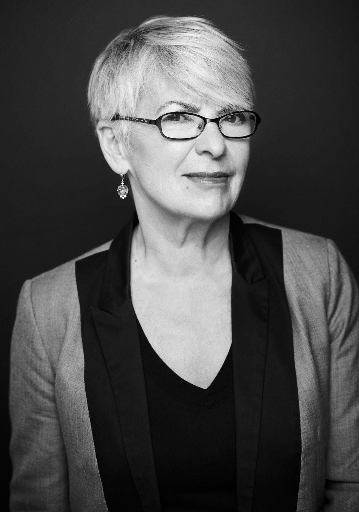 Black and white studio photograph of an older woman. She has very short gray hair, and she wears earrings, glasses, a black blouse, and a gray and black jacket. She smiles discreetly at the camera.