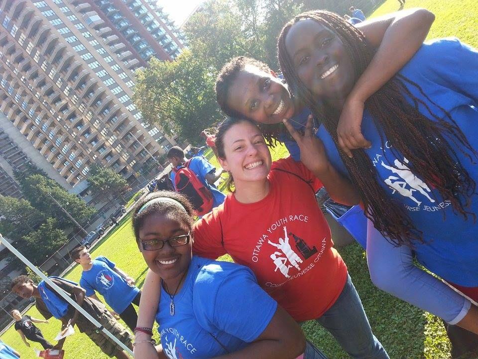 Photographie oblique en couleur de trois adolescentes noires en tee-shirt bleu et d'une jeune adulte blanche en tee-shirt rouge sur lequel apparaissent le logo et le nom de l'événement Ottawa Youth Race/Course Jeunesse Ottawa. À l'arrière-plan, un champ clôturé occupé par d'autres jeunes et de grands immeubles résidentiels.