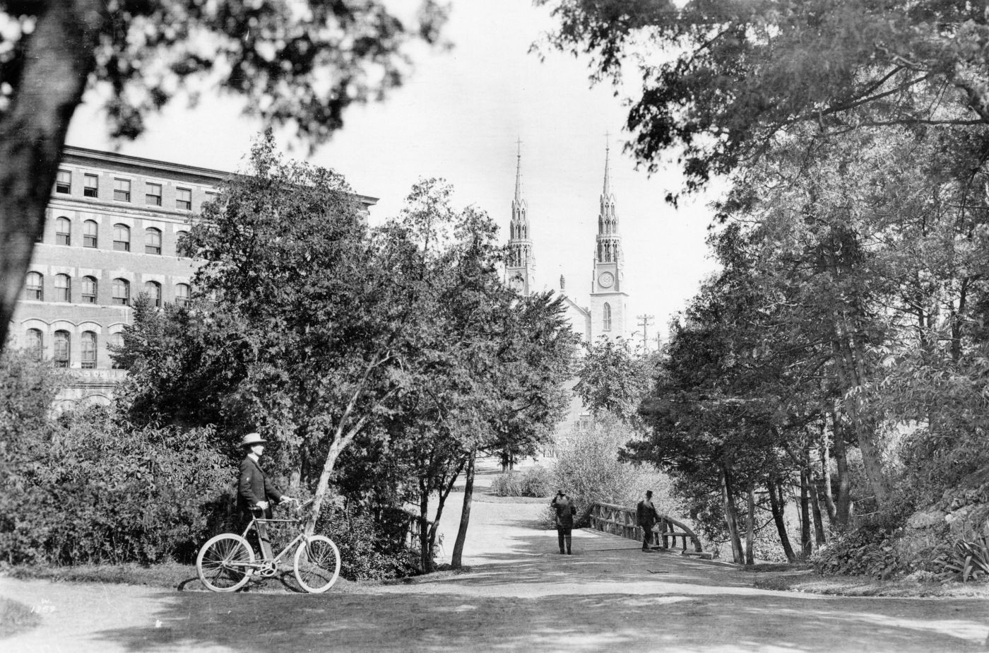 Black and white photograph showing a man walking beside his bicycle. He is moving toward a tree-lined esplanade leading to a wooden bridge. Two men are crossing the bridge on foot. Two steeples of a large church are visible in the background between the trees.