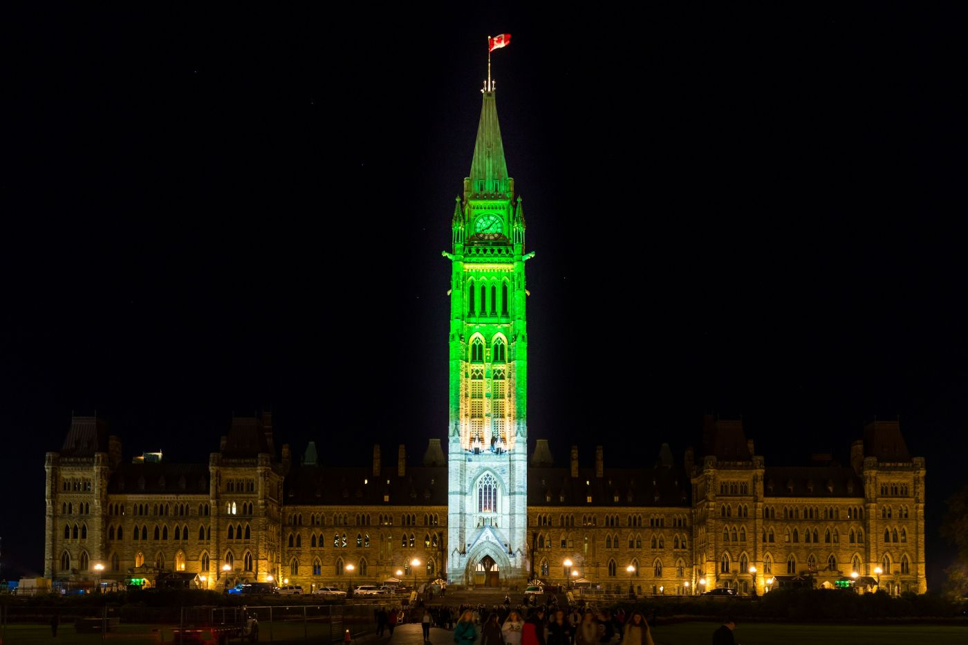 """"""" Colour photograph of a large, six-storey building at night. A Canadian flag flies at the top of the tower in the centre. The tower is illuminated in blue and green."""""""