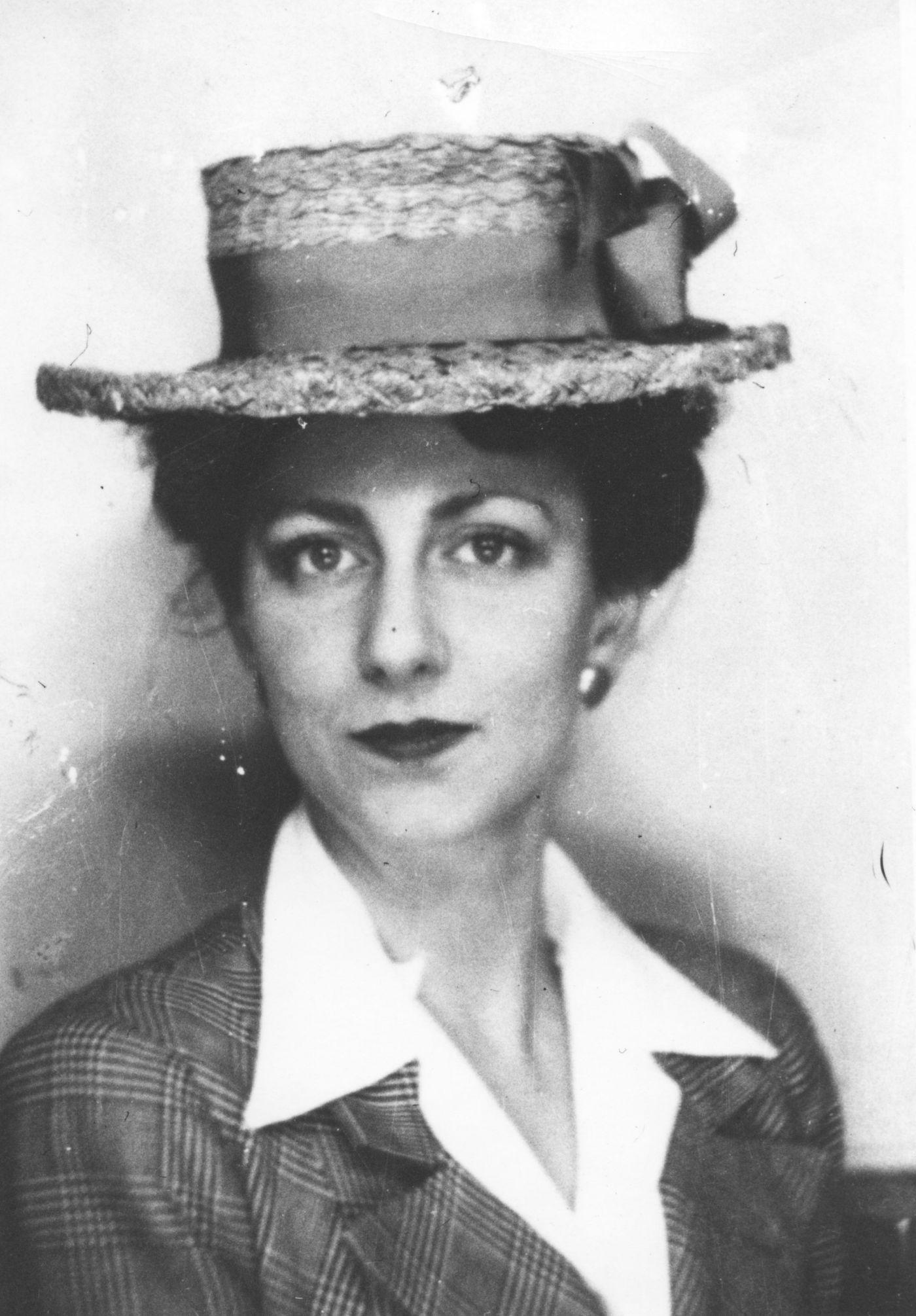 Portrait en noir et blanc d'une jeune femme. Elle a le regard très direct. Elle porte un élégant chapeau de paille décoré d'un large ruban ainsi qu'un veston de plaid et un chemisier blanc.