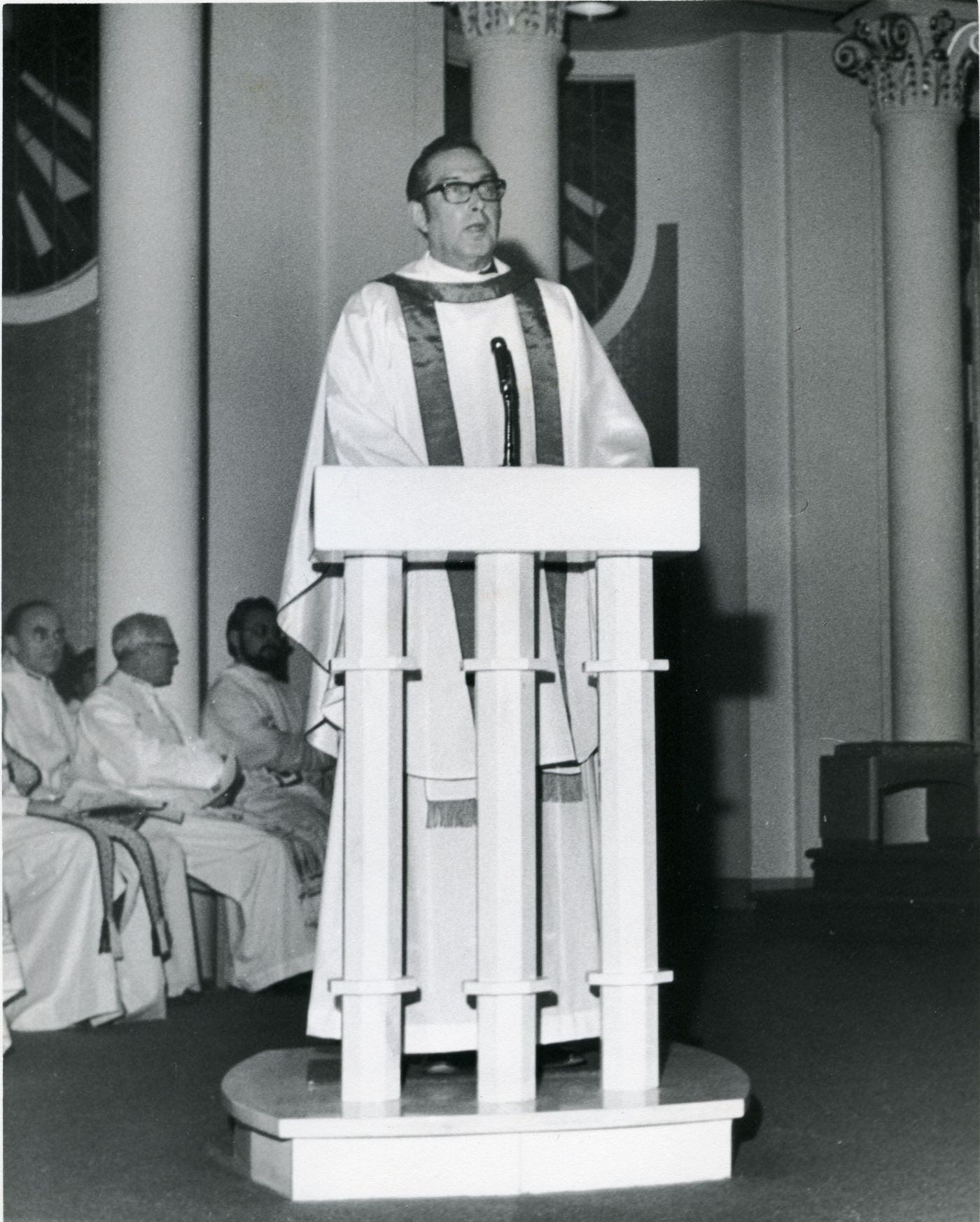 Black and white photograph of a priest clothed in white religious robes. He is standing at a church pulpit.