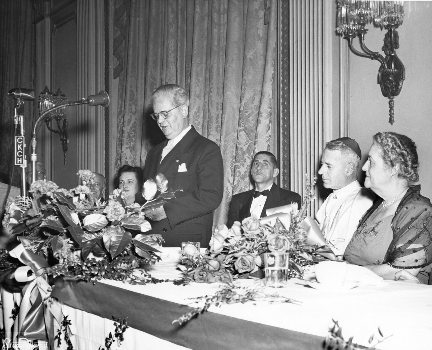 Photographie en noir et blanc d'un homme d'âge mûr en costume et cravate, debout, parlant devant un microphone. Une femme est assise à sa droite, un homme, un religieux portant la calotte et une autre femme sont assis à sa gauche, à une table décorée.