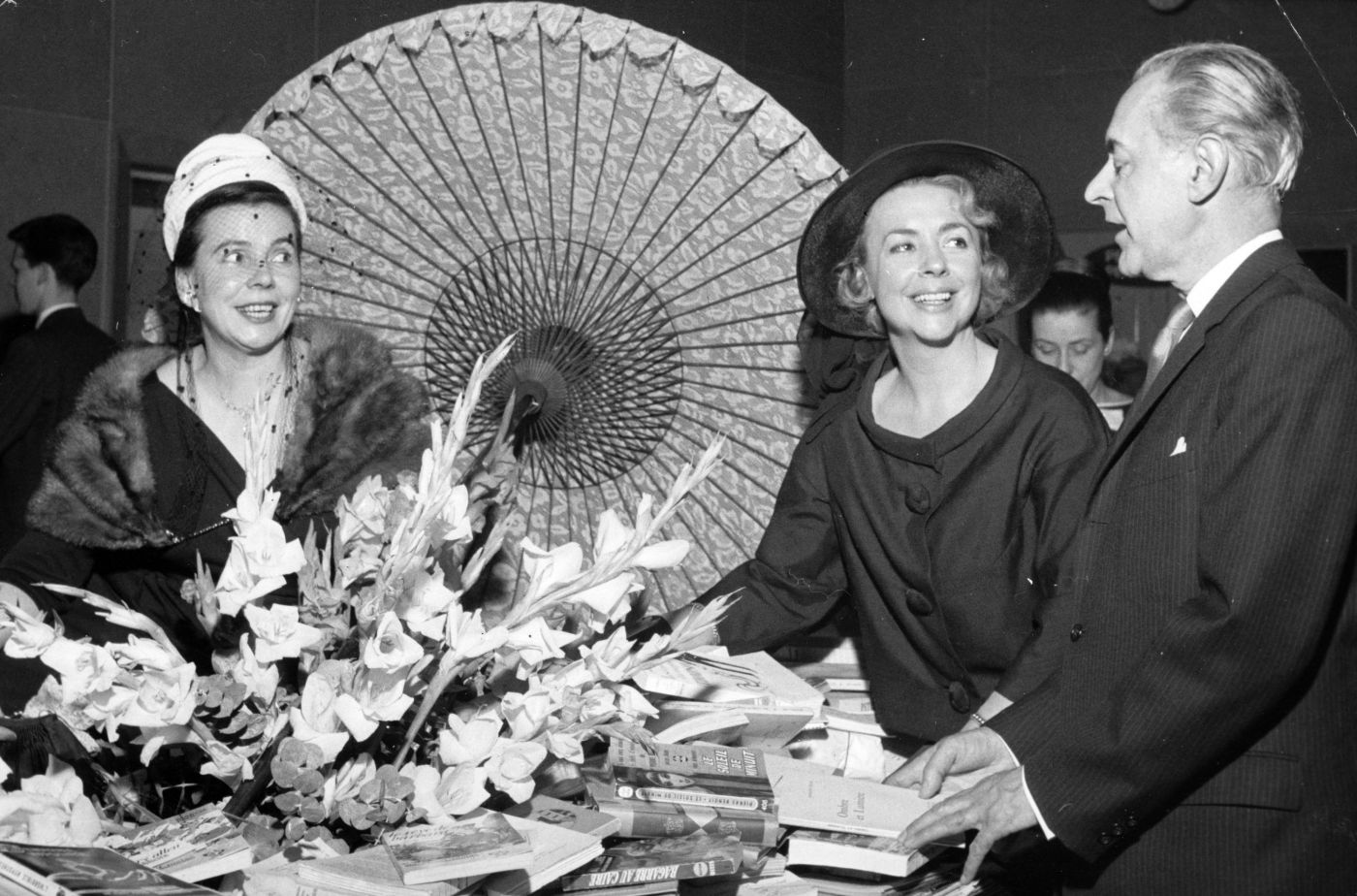 Black and white photograph of an older man, and two elegantly dressed, smiling middle-aged women. They are standing around a table with books piled around a large bouquet of flowers and an open parasol.