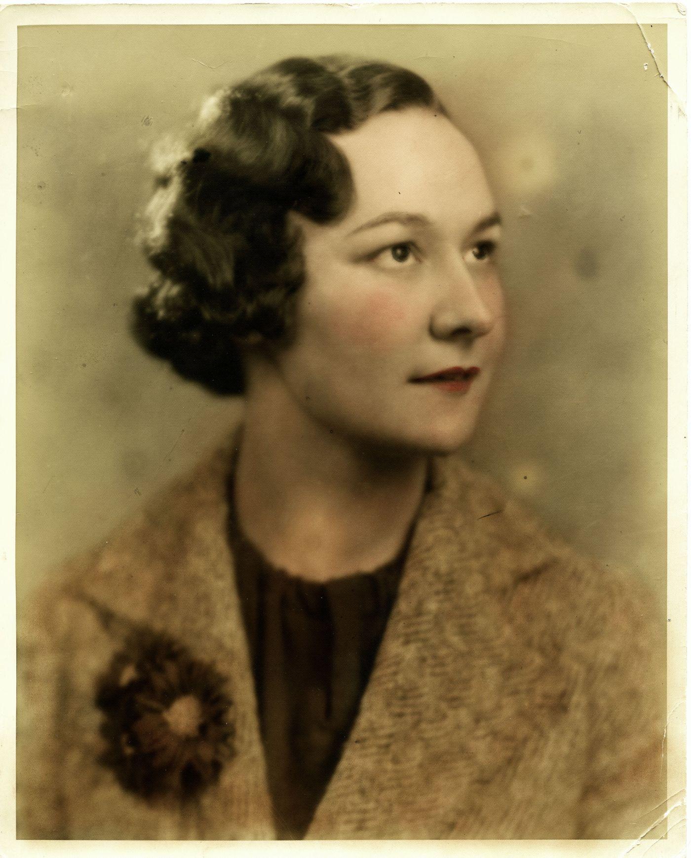 Photographie en couleur, gros plan, prise en studio, d'une femme d'âge moyen vue de profil aux trois quarts. Elle a les cheveux courts et ondulés et porte un veston avec des fleurs à la boutonnière.