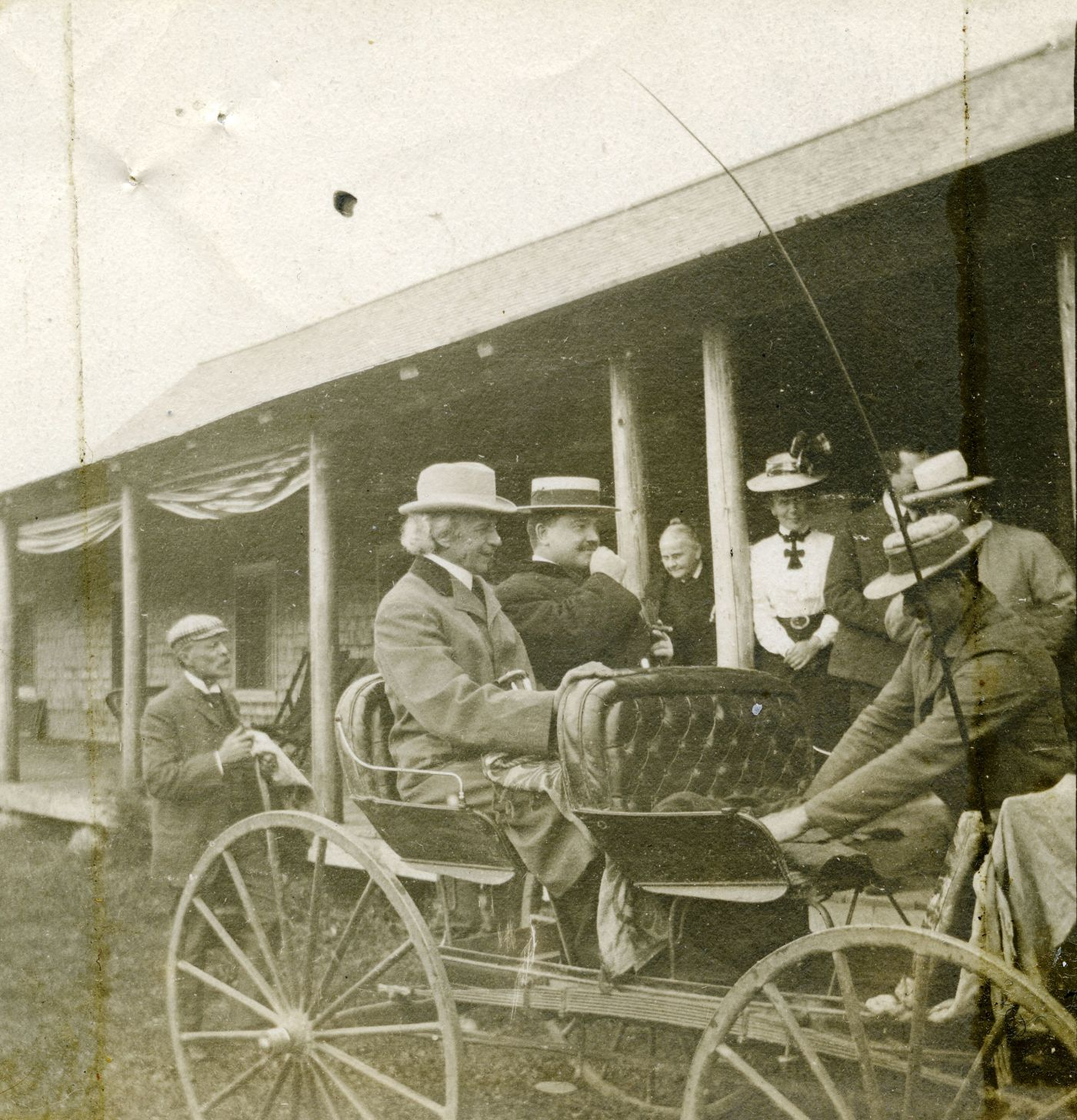 Black and white photograph of two well-dressed men sitting in a buggy in front of a wooden building. The white hair of the first is visible under his hat. The second, younger, wears a mustache. A third man prepares the buggy. Other people are watching them.