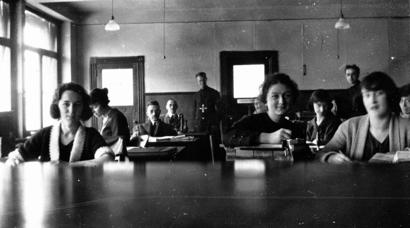 Photographie en noir et blanc d'hommes et de femmes assis à leur bureau. À l'avant-plan, trois jeunes femmes. Au fond de la salle, un homme debout portant des vêtements religieux.