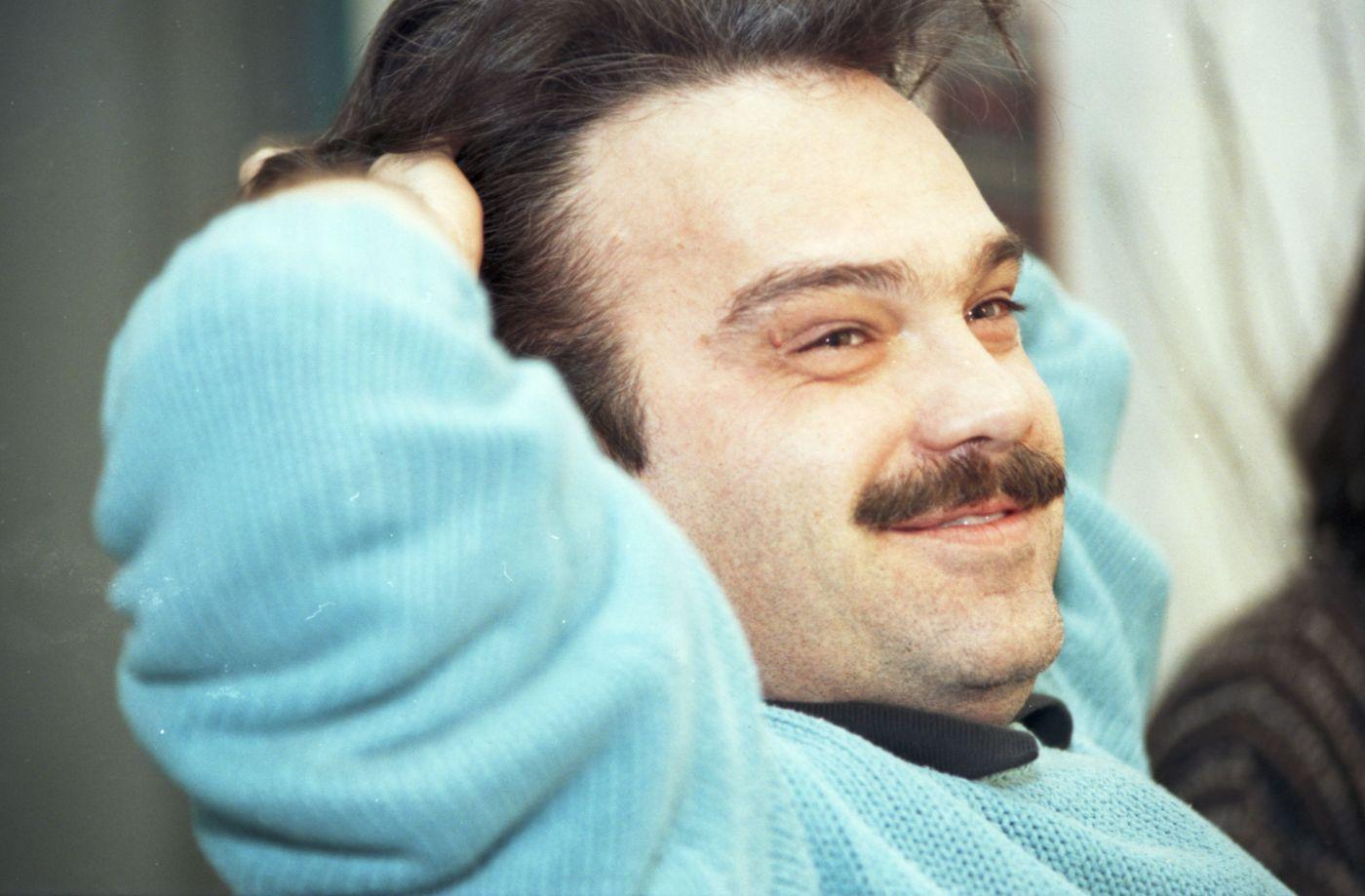 Photographie en couleur d'un homme d'âge moyen souriant, vu de trois quarts. Il est assis, les deux mains derrière la tête. Il a les cheveux bruns et une moustache. Il porte un chandail bleu pâle.