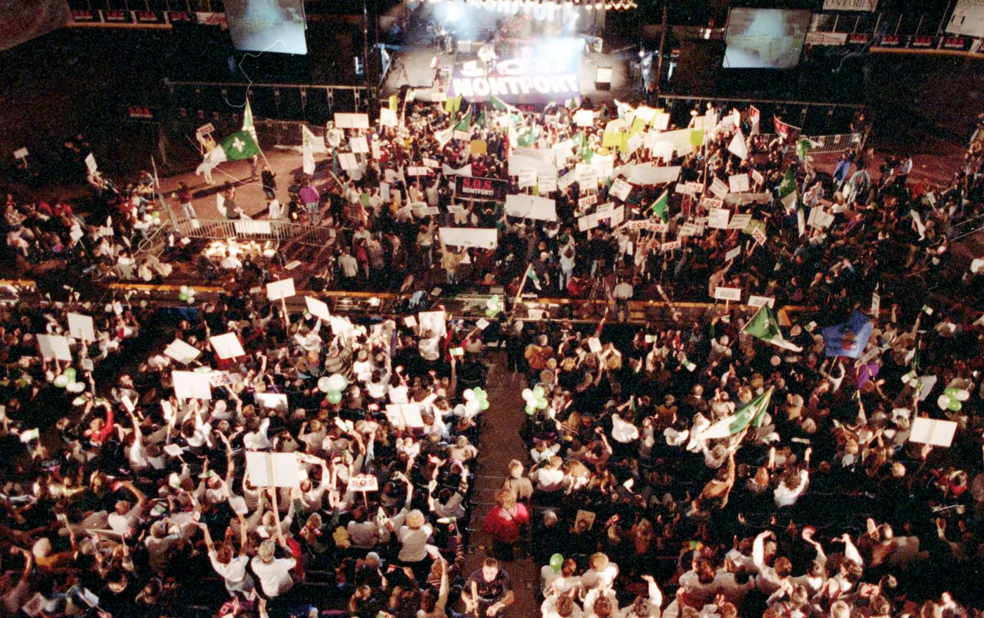 """Colour photograph of a large crowd, seen from behind, in front of a stage. The words """"S.O.S. Montfort"""" are visible on the floor of the stage. The crowd is waving Franco-Ontarian flags, green and white balloons, and placards with the """"S.O.S. Montfort"""" slogan."""