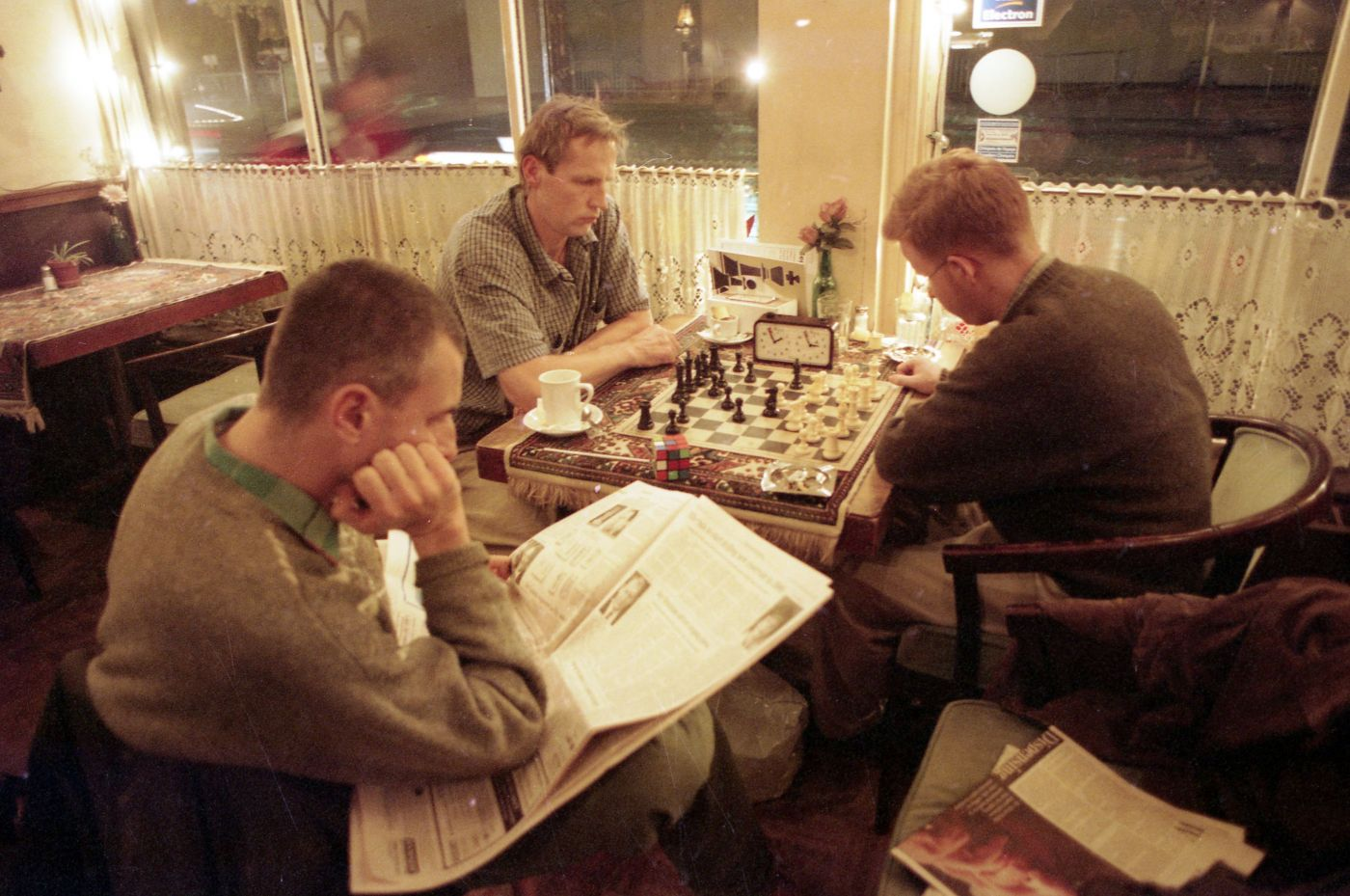 Colour photograph of three middle-aged men sitting in a cafe in the evening. Two of the men are playing chess. The third man is reading a newspaper at their side.
