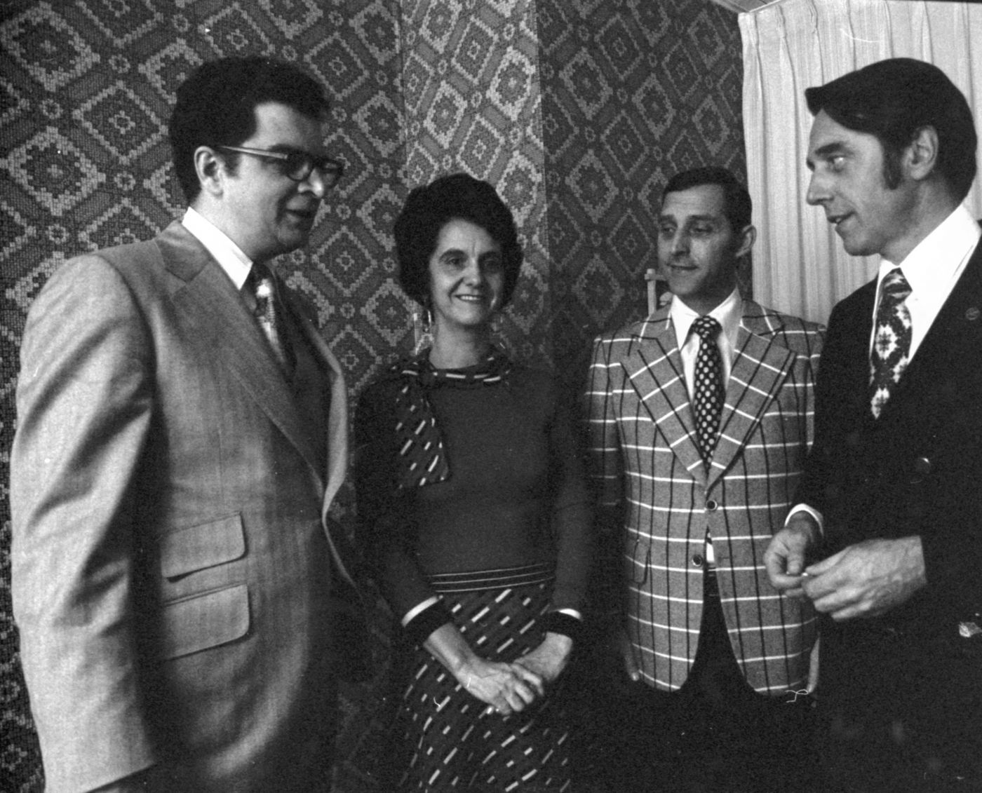 Black and white photograph of three men and a woman, middle-aged, talking. They are standing in a living room. The men wear jackets and ties; the woman wears a dress.