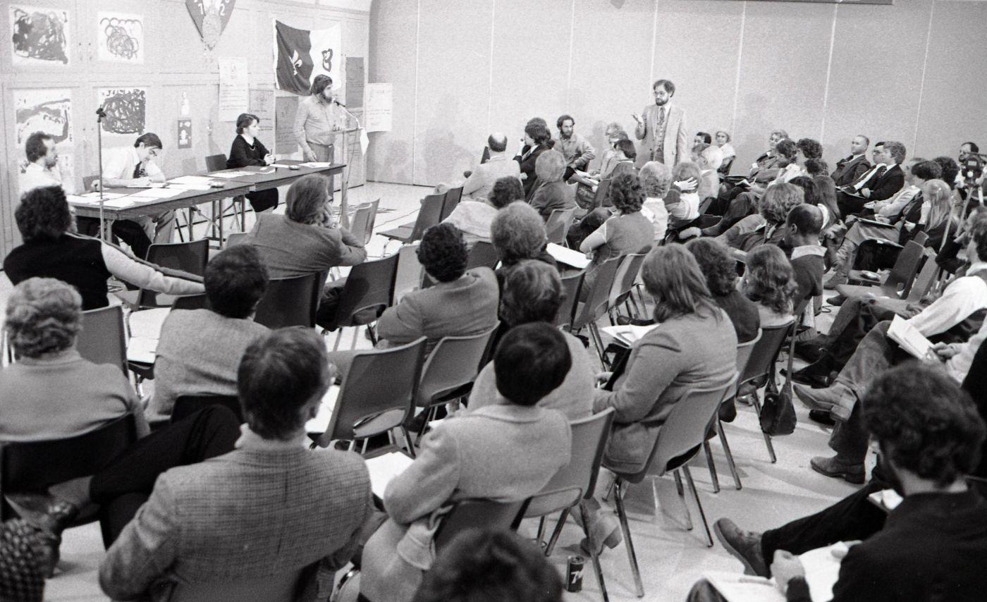 Photographie en noir et blanc d'une réunion à laquelle participent des dizaines de personnes, vues de dos. Devant elles, trois intervenants, dont une femme, sont assis à une table sur laquelle sont déposés des documents. Un quatrième est debout au micro. Il s'adresse visiblement à un des participants, qui s'est levé durant l'échange. Le mur qui fait face à la salle est tapissé d'affiches. Le drapeau franco-ontarien y est accroché.