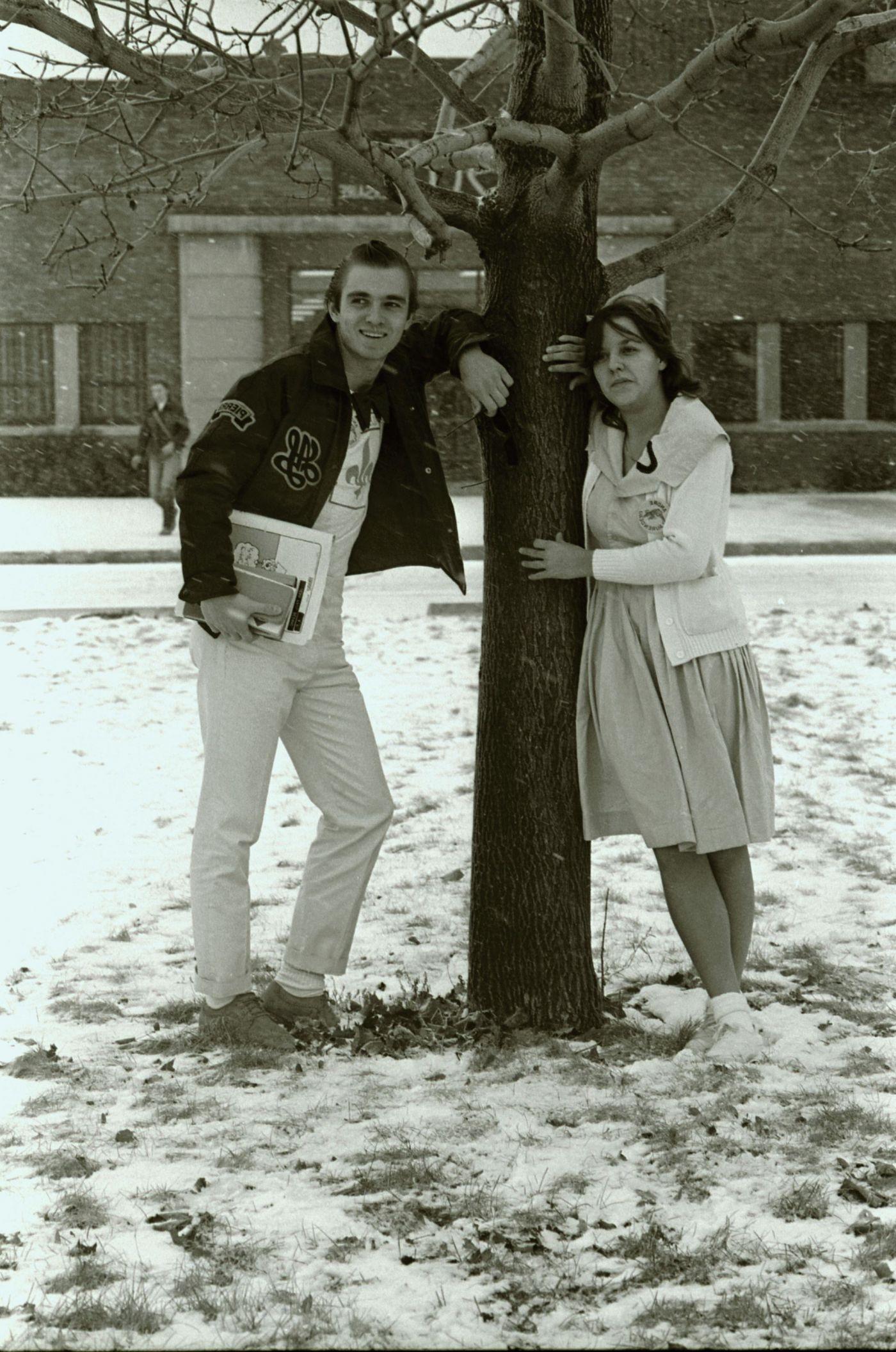Photographie en noir et blanc d'un adolescent et d'une adolescente, dehors devant un édifice en brique. Ils s'appuient de façon décontractée contre un arbre en hiver. Il porte une veste en cuir et une chemise arborant une fleur de lys, tandis qu'elle porte une robe avec un grand col et une veste blanche.