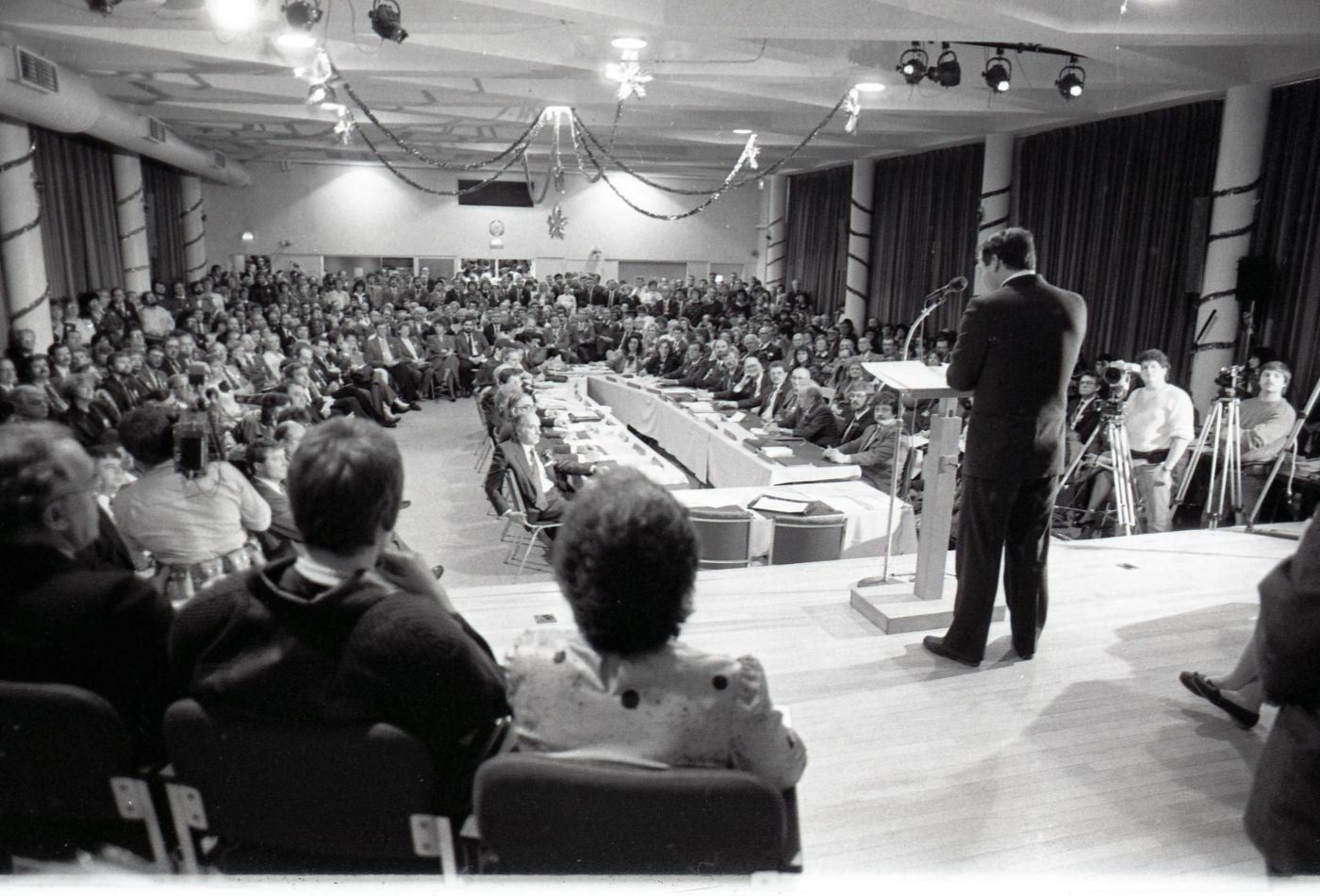 Photographie en noir et blanc d'un homme vu de dos en costume, debout sur une scène et parlant au microphone. Il s'adresse à un public nombreux dans une salle comble et à des journalistes.