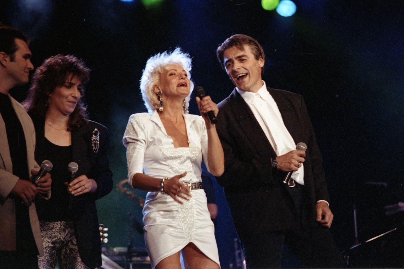 Photographie en couleur d'un groupe de quatre chanteurs, sur scène. Une femme d'âge mûr, en robe blanche courte et portant des bijoux, chante avec un microphone à la main, accompagné d'un homme d'âge moyen en complet noir et chemise blanche. À leur droite, un homme et une femme d'âge moyen tiennent des microphones.
