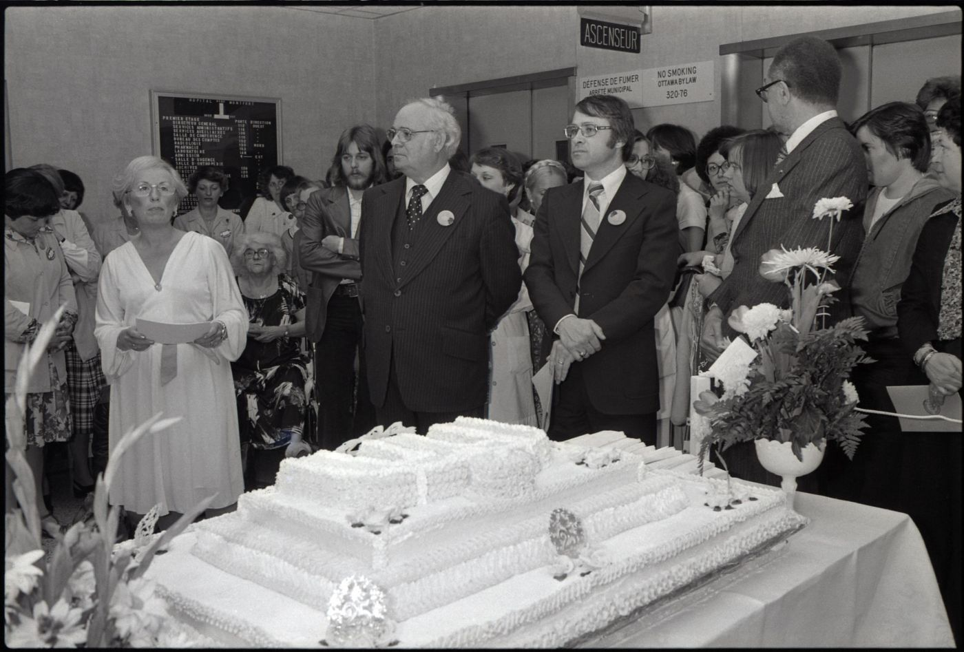 Black and white photograph of a group of people standing around a huge cake decorated with the logo of the Montfort Hospital. Two wreaths of flowers are placed on the table. In the foreground, three men in suits wearing the same button, and an elegantly dressed woman holding a sheaf of papers.