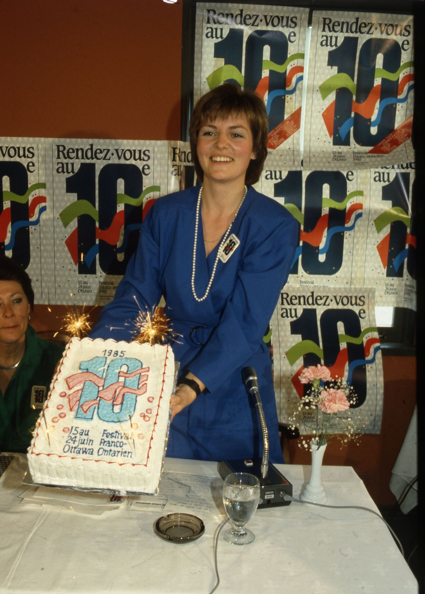 """Colour photograph of a middle-aged, smiling woman with short brown hair, wearing a blue dress. She holds up a cake decorated with a large number 10, a date, and the words """"Festival Franco-Ontarien."""" Behind her, a wall covered with 10th anniversary promotional posters."""