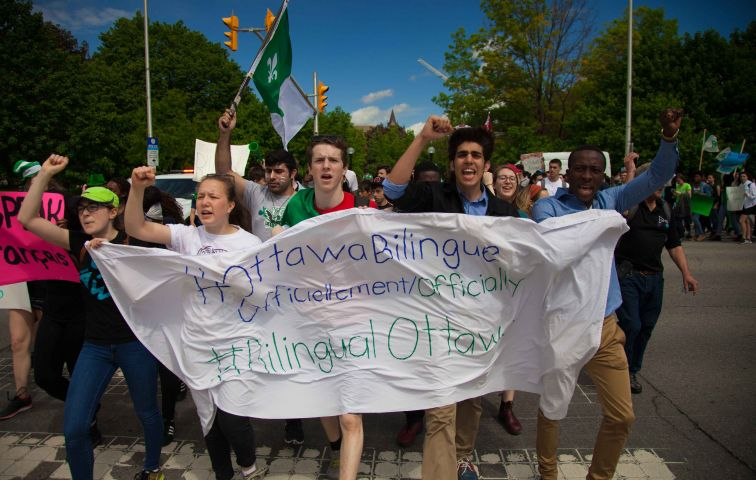 """Colour photograph of five young people, fists raised, walking briskly, holding a banner with the slogan: """"Ottawa bilingue officiellement/Officially bilingual Ottawa"""". Behind them, other protesters walk down the street waving flags and carrying placards."""