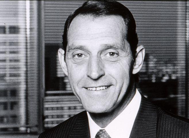 Photographie en noir et blanc d'un homme d'âge moyen souriant, en costume-cravate. L'homme est devant une fenêtre, avec vue sur des édifices en hauteur.