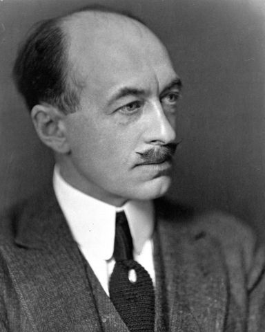 Black and white studio photograph of a mature, balding man with a mustache, in three-quarter view. He wears a gray suit, with a black tie and white tie pin, along with a serious expression.